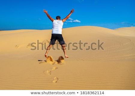 Belo moço saltando descalço areia deserto Foto stock © galitskaya