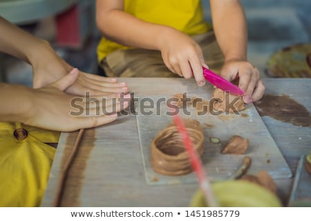 mother and son doing ceramic pot in pottery workshop. What to do with children. Child friendly place Stock photo © galitskaya
