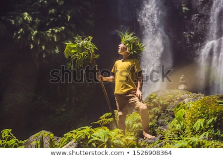 Cute boy depicts the king of the jungle against the backdrop of a waterfall. Childhood without gadge Stock photo © galitskaya