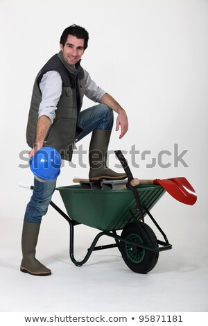 construction worker showing off his hard hat wheelbarrow and tools stock photo © photography33