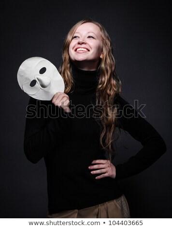 Low key portrait of a beautiful woman holding mask Stock photo © dashapetrenko
