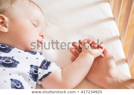 Portrait of a cute baby sleeping peacefully in his mother's arms lying in the sofa at home Stock photo © wavebreak_media