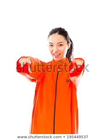 Young Asian woman smiling in prisoners uniform with finger in mouth Stock photo © bmonteny