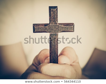 male hands holding wooden cross on white background stock photo © deandrobot