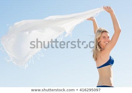 Beautiful smiling blonde holding scarf at the beach Stock photo © wavebreak_media