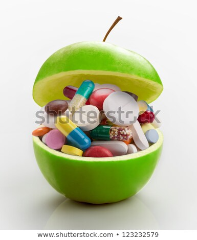 Stock photo: Natural green apple and various colored pills