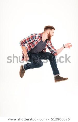 Fiatal szakállas férfi ugrik játszik láthatatlan Stock fotó © deandrobot