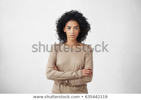 Triste chateado mulher jovem em pé brasão dobrado Foto stock © deandrobot