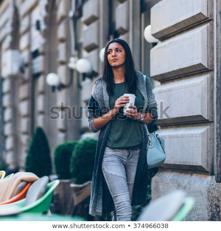 Cute young woman drinking take away coffee. Stock photo © deandrobot