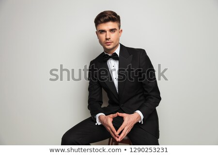 seated man in tuxedo and bowtie holding palms together  Stock photo © feedough