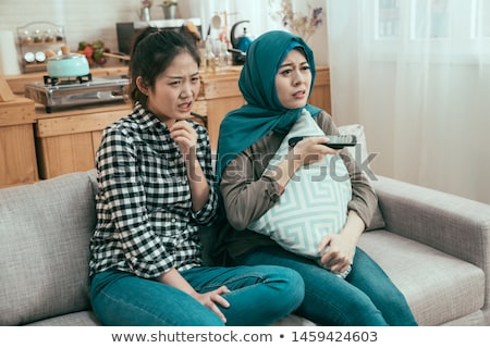 Nervous multi-ethnic friends watching TV at home Stock photo © wavebreak_media