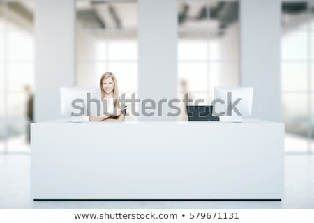 Stock photo: Smiling girl in front of a checkin desk