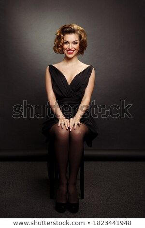 portrait of seated attractive woman wearing makeup smiling Stock photo © feedough