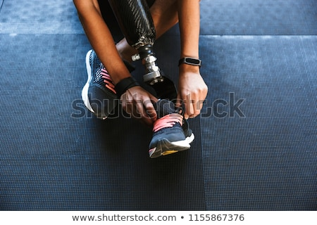 Disabled sports woman tie her laces in gym. Stock photo © deandrobot