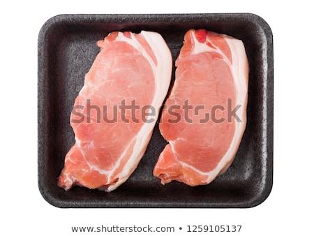 Raw pork loin chops in plastic tray on white background. Stock photo © DenisMArt
