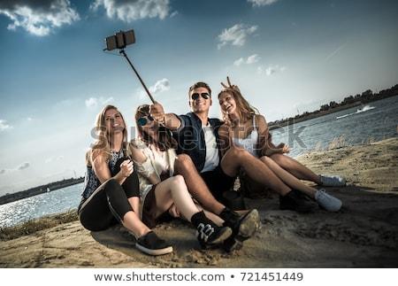 hippie friends taking picture by selfie stick stock photo © dolgachov