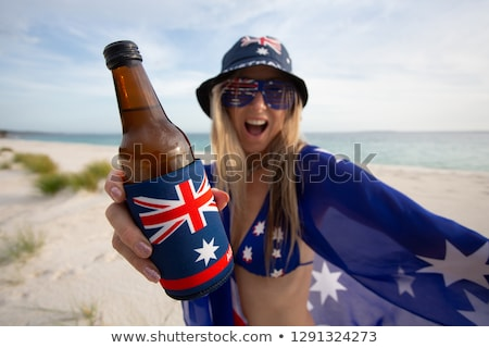 Australian woman holding a flag and beer bottle celebrating Aust Stock photo © lovleah
