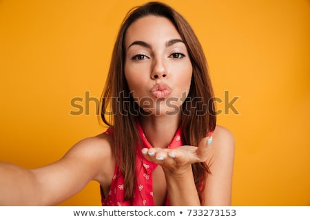 Studio portrait of a beauty young pretty, brunette woman sending blowing kisses at camera and posing stock photo © studiolucky