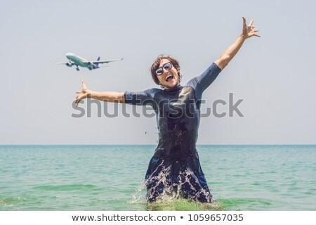 A man bathes in the sea, an airplane lands Stock photo © galitskaya