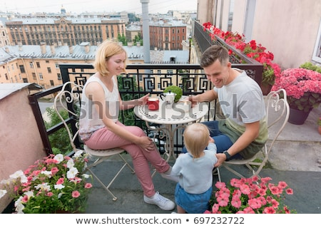 Happy family having breakfast on the balcony. Breakfast table with coffee fruit and bread croisant o Stockfoto © galitskaya