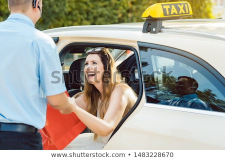 Taxi driver helping woman passenger out of the car Stock photo © Kzenon