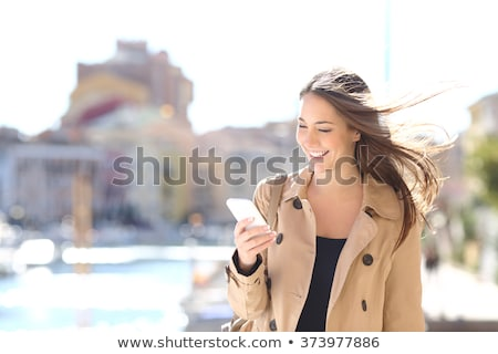 smiling woman using mobile phone on beach stock photo © andreypopov