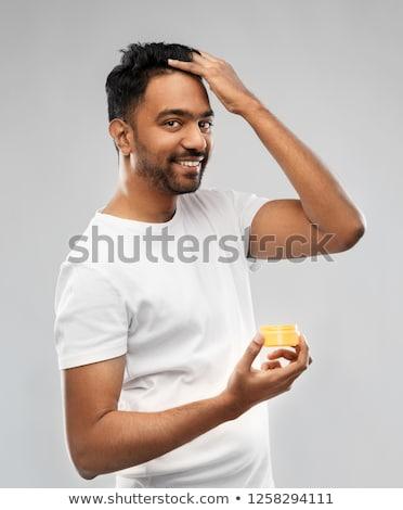 indian man applying hair wax or styling gel Stock photo © dolgachov