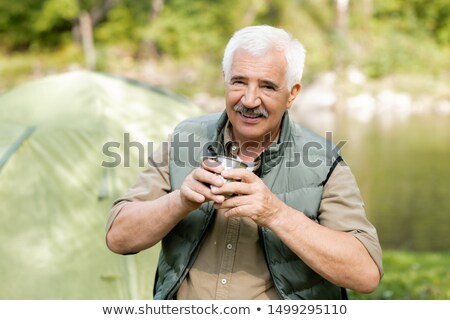 Happy senior active man with hot drink looking at you while enjoying his trip Stock photo © pressmaster