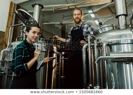 man with clipboard at craft brewery or beer plant Stock photo © dolgachov