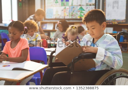 Side view of disable schoolboy with classmates studying and sitting at desk in classroom of elementa Stock photo © wavebreak_media
