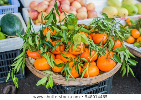 Asian farmer market selling fresh Mandarin in Hoi An, Vietnam. Orange and green colors. Stock photo © galitskaya