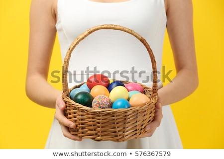 happy girl with colored eggs in wicker basket Stock photo © dolgachov