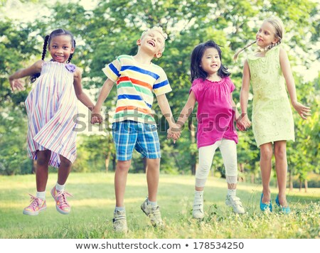 Diversity friends jumping in the park Stock photo © Kzenon