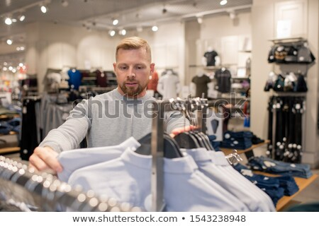 Young handsome shopper looking at white shirt on rack while choosing one Stock photo © pressmaster