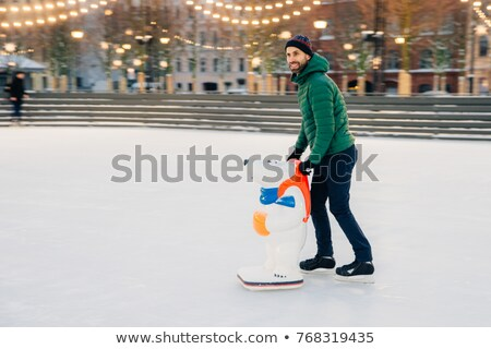 Pleased male skater being on skating ring, uses skate aid as tri Stock photo © vkstudio