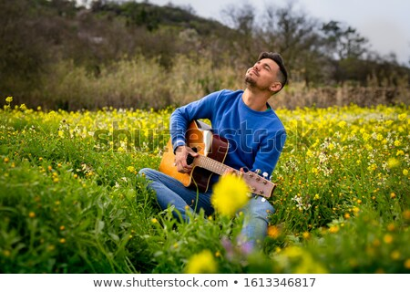 young man plays on guitar on grass Stock photo © Paha_L