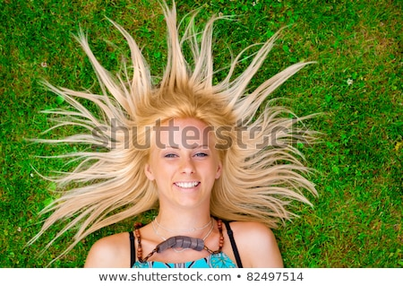 young woman laying on green grass with hair like a sun around he stock photo © hasloo