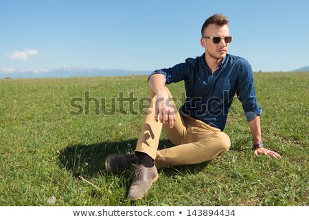 casual man laying in the grass and looking away stock photo © feedough
