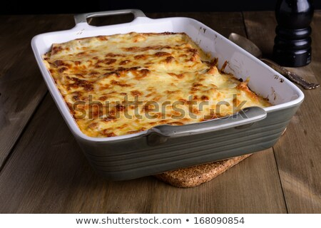 Lasagna in a serving plate with cheese on top on an old wood tab Stock photo © phila54