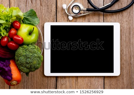 Stethoscope and green apple isolated on Tablet Stock photo © rufous