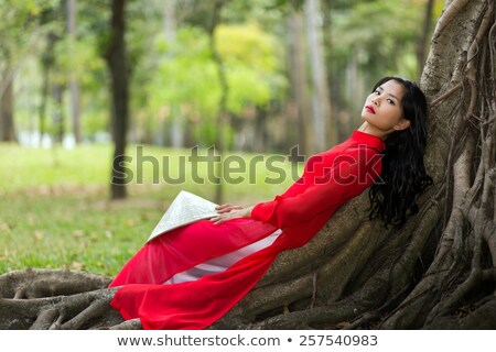 Pretty Vietnamese lady relaxing on tree roots Stock photo © smithore