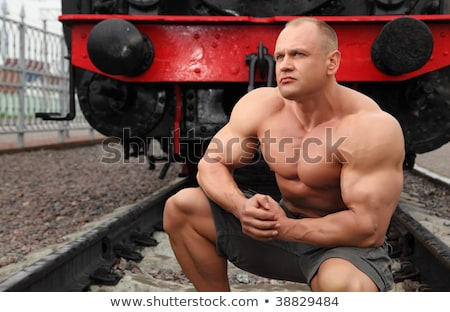 strong shirtless man sits on railroad against locomotive stock photo © Paha_L
