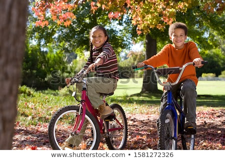 Girl riding bike at park on sunny fall season stock photo © cienpies
