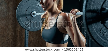 Close-up portrait of a woman doing squats with barbell Stock photo © deandrobot