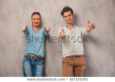 casual blonde woman standing and showing thumbs up gesture stock photo © deandrobot
