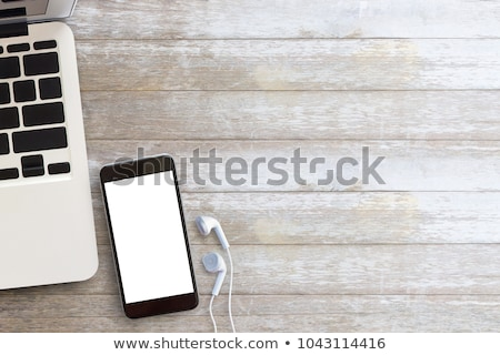 Top view of smartphone with black screen laptop and earphones Stock photo © deandrobot