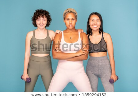 Woman standing with dumbbells and looking at camera Stock photo © deandrobot