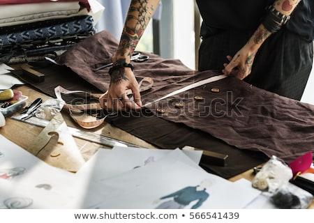 fashion designer cutting fabric at studio Stock photo © dolgachov
