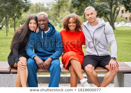 Happy young asian man dressed in hoodie sitting on a bench Stock photo © deandrobot