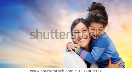 happy mother and daughter hugging over evening sky Stock photo © dolgachov